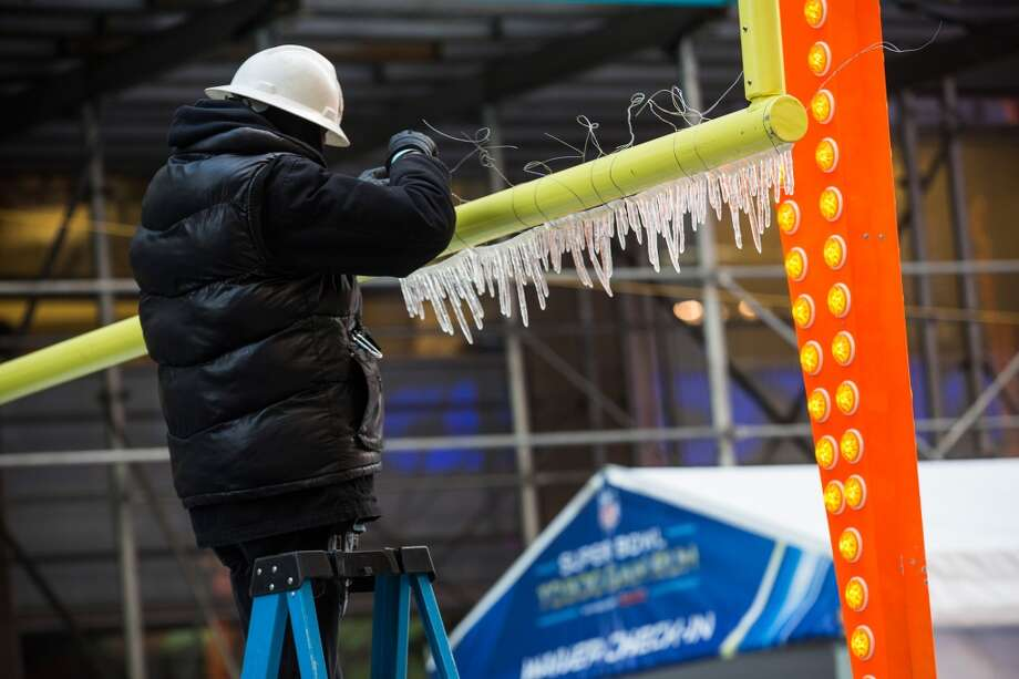 "A worker attaches fake icicles to a goal post for ""Super Bowl Boulevard,"" which runs through Times Square and down Broadway, on January 28, 2014 in New York City. In preperation for the Super Bowl, this Sunday in East Rutherford, NJ, the city is turning sections of Times Square and Broadway into 'Super Bowl Boulevard,' which will feature events such as games, concerts and live broadcasts. Photo: Andrew Burton, Getty Images"