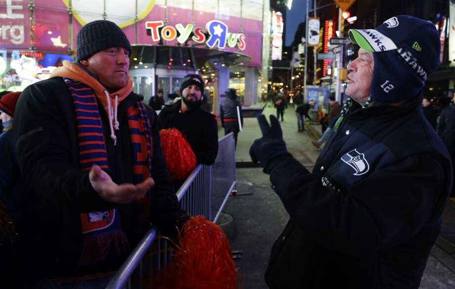 Seattle Seahawks fan Lynn Thomas, right, of Seattle, jokes with Denver Broncos fan Aaron Cassel, left, of Denver, Colo., about the possible outcome of the Super Bowl, Friday, Jan. 31, 2014 at Times Square in New York. The Seattle Seahawks will play the Broncos Sunday in the NFL Super Bowl XLVIII football game in East Rutherford, N.J. Photo: Ted S. Warren, Associated Press