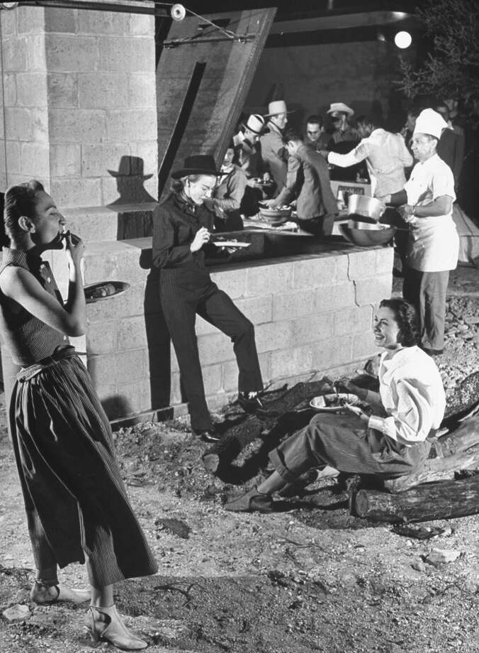 Guests at Texas' Flying L Ranch sharing a cookout and wearing many fashions, 1947. Photo: Cornell Capa, Time & Life Pictures/Getty Image