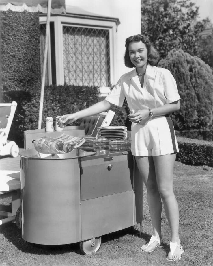 American actor Jane Wyman seasons steaks over the grill of her portable Huntington barbecue in her backyard in 1949. Photo: Hulton Archive, Getty Images