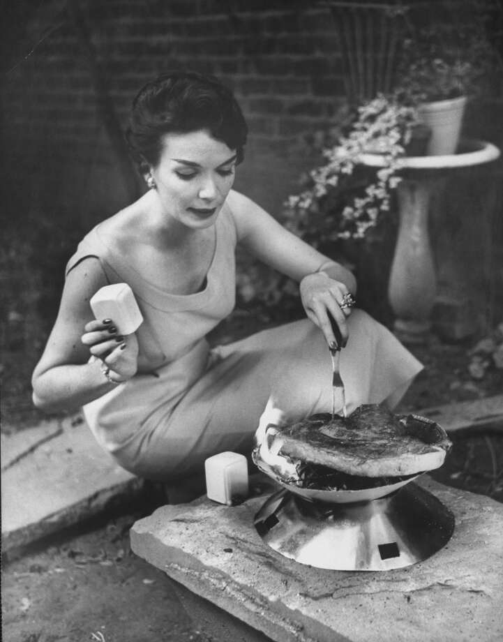 A woman cooking steak on a disposable barbecue grill in 1955. Photo: Peter Stackpole, Time & Life Pictures/Getty Image