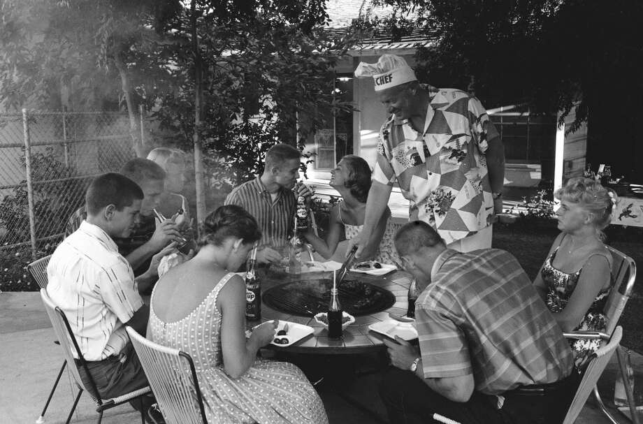 Teenager Suzie Slattery talking with boyfriend Ted Sten while her father serves barbeque to party guests, 1959. Photo: Yale Joel., Time & Life Pictures/Getty Image