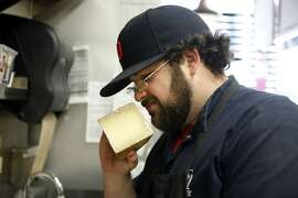 Cheesemonger Zach Berg smells a piece of Ardi Gasha cheese for freshness while working behind the counter at Bi-Rite Market on Divisadero St. in San Francisco, CA, Tuesday, January 28, 2014.