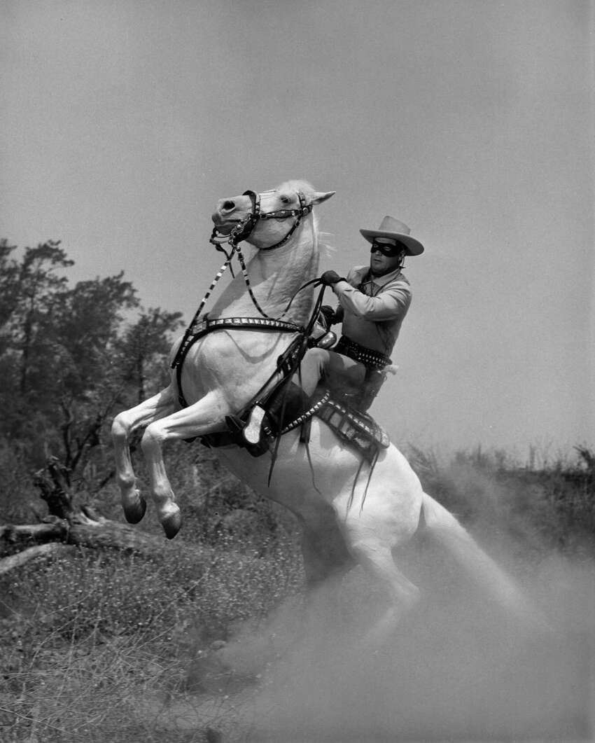 circa 1955: American actor Clayton Moore, in masked costume as 'The Lone Ranger,' rears back on his horse, Silver, in a still from the American television series, 'The Lone Ranger'.