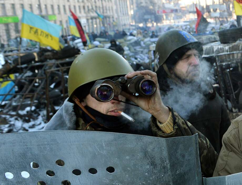 An opposition protester uses a helmet and binoculars to guard a roadblock in downtown Kiev. Photo: Sergei Supinsky, AFP/Getty Images