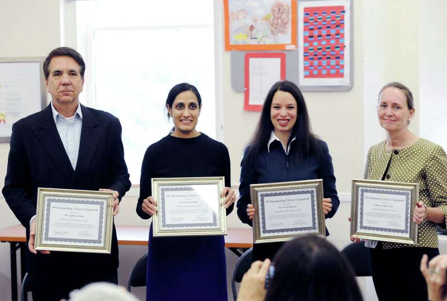 Hamilton Avenue School parents who helped to save the life of another parent who had a heart attack during an October Common Core workshop are from left, Anthony Perna, Dr. Setul Pardanani, Dr. Leora Horwitz, and Caitriona Perna (Anthony Perna's wife), a registered nurse, were honored during a ceremony at the Greenwich Board of Education Building, Friday afternoon, Jan. 31, 2014. Photo: Bob Luckey / Greenwich Time