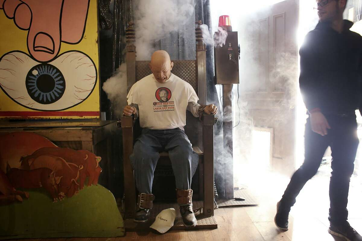 Bob Pritikin's assistant Chris Johnson stands back after turning on the dummy in an electrocution chair in a downstairs room of The Pritikin Museum in San Francisco, Calif.