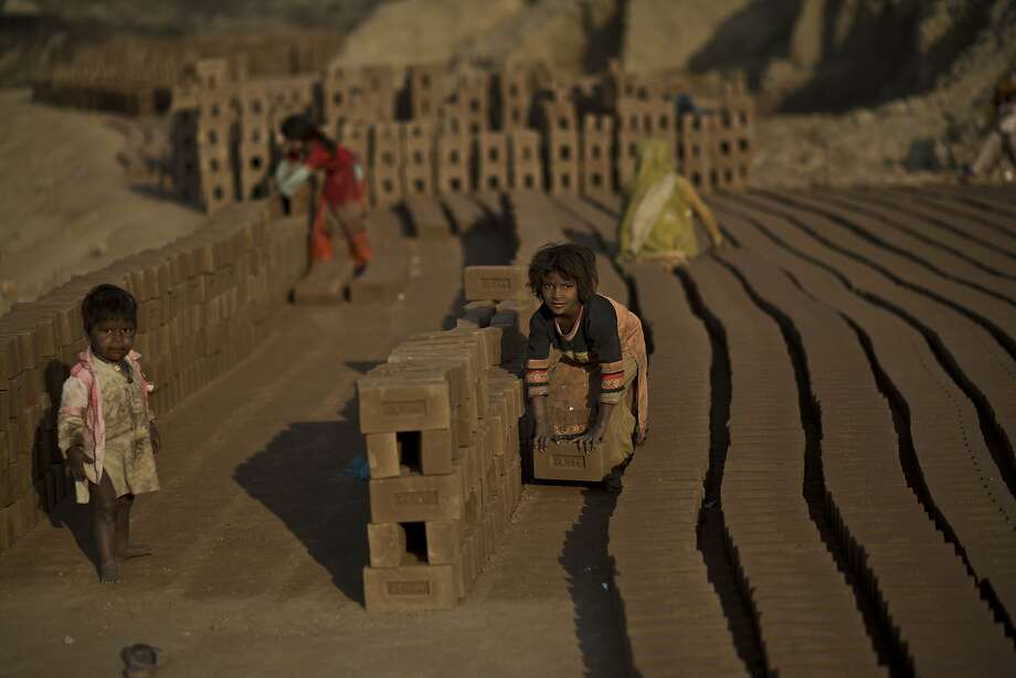 Lost childhood: A Pakistani girl (center) stacks bricks while keeping an eye on her baby brother 