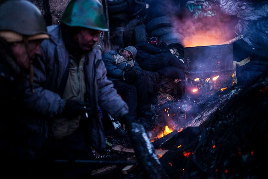 Ultimatum in Kiev:Anti-government protesters warm themselves at a fire near a barricade in Kiev. A 