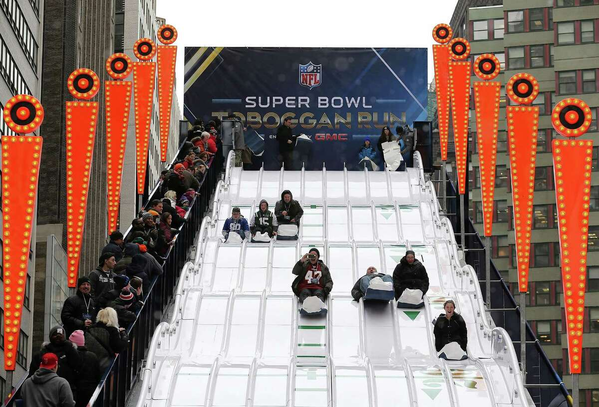 NEW YORK CITY, NY - JANUARY 31: People slide down the NFL toboggan run in Times Square on January 31, 2014 in New York City. Broadway has temporarily been re-named Super Bowl Boulevard as the city prepares for Sunday's game between the Denver Broncos and Seattle Seahawks. (Photo by Christian Petersen/Getty Images) ORG XMIT: 465295387