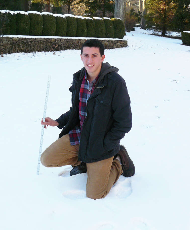 Scott Pecoriello, 17, takes measurements of the snow in hisi backyard. The teen has built an app that predicts when bad weather will close area schools. Photo: Staff Photo/Gretchen Webster / Westport News