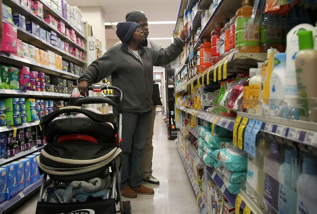 """Gertrude, 34, left, and Carine, 30, study different kinds of baby formula for their daughter Princess, 1, (in the stroller) in an aisle at Walgreens Jan. 17, 2014 in San Francisco, Calif. The couple preferred to use only their first names for safety reasons. Gertrude and Carine have both been granted asylum in the U.S. after fleeing their home country of Cameroon with their baby daughter, Eldine """"Princess"""", to avoid legal persecution and people who would have them killed because they are lesbians. After Gertrude was one of a cast of characters featured in a documentary about being part of the secretive LBGT community in Cameroon, she began receiving death threats and opted to stay in America in July while she was in the country promoting the film in L.A. Her girlfriend Carine remained in Cameroon with their daughter Princess and was forced to go into hiding for their safety until they were able to make it to San Francisco in November. Though both of the women have been granted asylum, they are still waiting on Princess' status. The family are currently staying in a shelter in the Tenderloin, using resources from their lawyer and other community members to get by until they can find employment."""