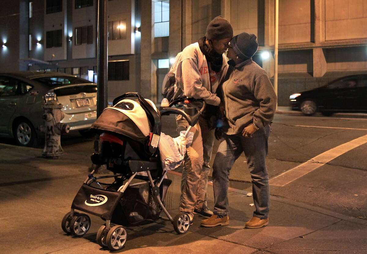 """Carine, 30, left, goes in for a kiss with Gertrude, 34, after some coaxing while the two stop at the corner before going home with their daughter Princess, 1, to the Hamilton Family Center Jan. 17, 2014 in San Francisco, Calif. The couple preferred to use only their first names for safety reasons. Though it's now perfectly legal for the two to be together, Carine still struggles with showing outward affection for Gertrude due to her experiences in Cameroon. Gertrude and Carine have both been granted asylum in the U.S. after fleeing their home country of Cameroon with their baby daughter, Eldine """"Princess"""", to avoid legal persecution and people who would have them killed because they are lesbians. After Gertrude was one of a cast of characters featured in a documentary about being part of the secretive LBGT community in Cameroon, she began receiving death threats and opted to stay in America in July while she was in the country promoting the film in L.A. Her girlfriend Carine remained in Cameroon with their daughter Princess and was forced to go into hiding for their safety until they were able to make it to San Francisco in November. Though both of the women have been granted asylum, they are still waiting on Princess' status. The family are currently staying in a shelter in the Tenderloin, using resources from their lawyer and other community members to get by until they can find employment."""