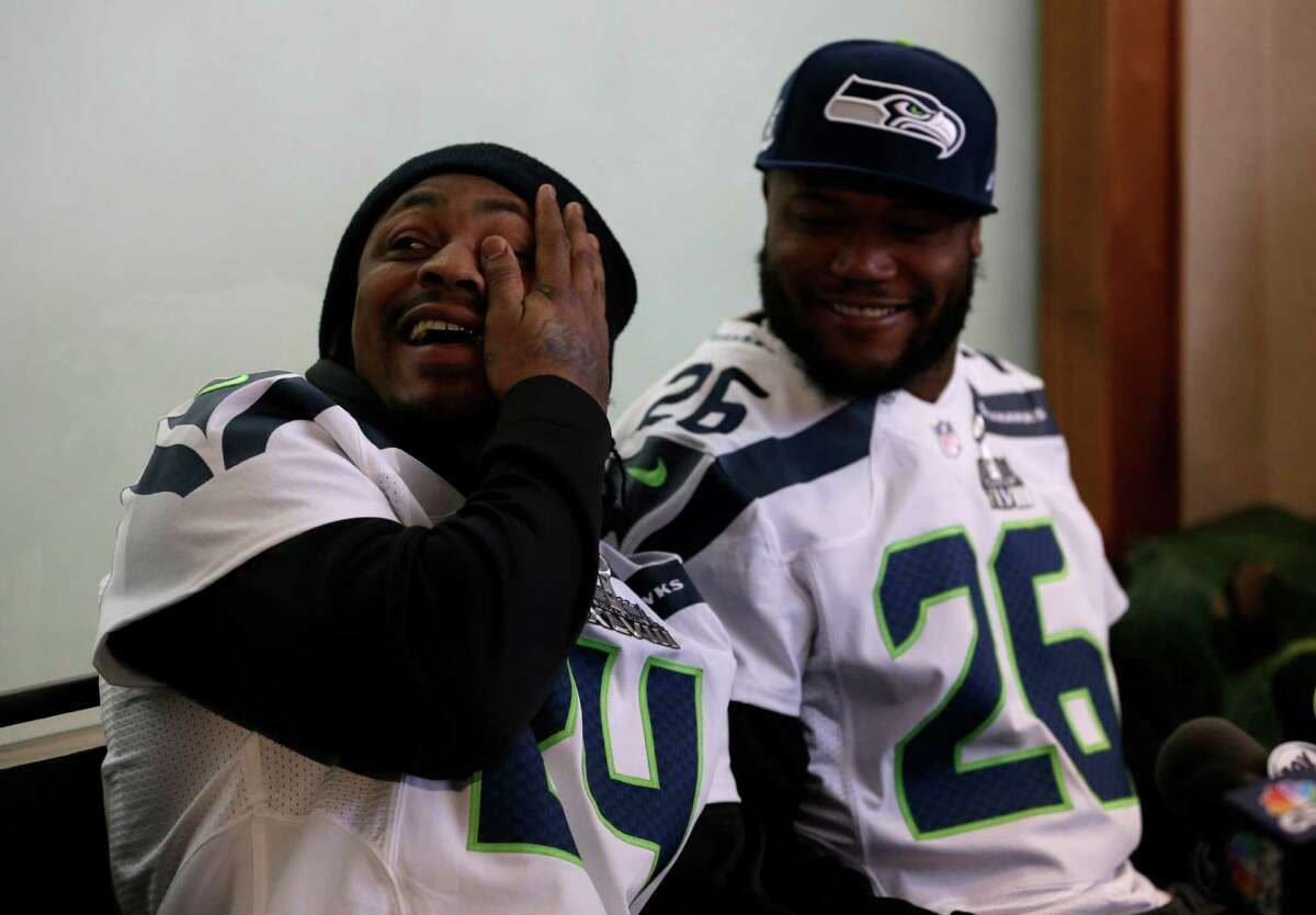 Seattle Seahawks running back Marshawn Lynch, left, laughs along side teammate Michael Robinson as they participate in a media availability Thursday, Jan. 30, 2014, in Jersey City, N.J. The Seahawks and the Denver Broncos are scheduled to play in the Super Bowl XLVIII football game Sunday, Feb. 2, 2014. (AP Photo)