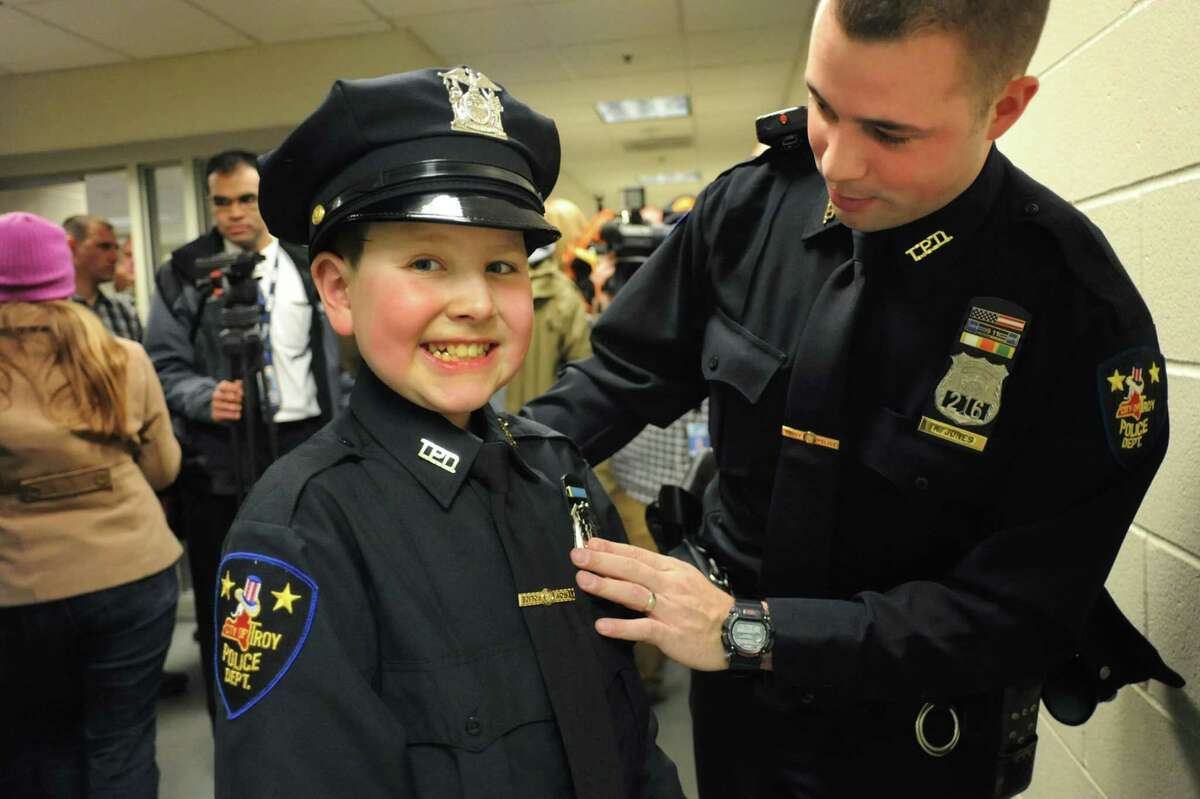 J.P. Honsinger, 10, of Clifton Park, center, gets his badge pinned on from Officer Kyle Jones on Friday, Jan. 31, 2014, at Troy Police Headquarters in Troy, N.Y. J.P., who has Niemann-Pick disease, was named an honorary member of the police force. (Cindy Schultz / Times Union)