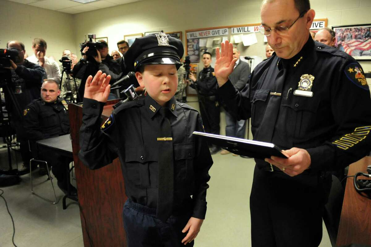 J.P. Honsinger, 10, of Clifton Park, center, takes the oath of police officer from Chief John Tedesco on Friday, Jan. 31, 2014, at Troy Police Headquarters in Troy, N.Y. J.P., who has Niemann-Pick disease, was named an honorary member of the police force. (Cindy Schultz / Times Union)