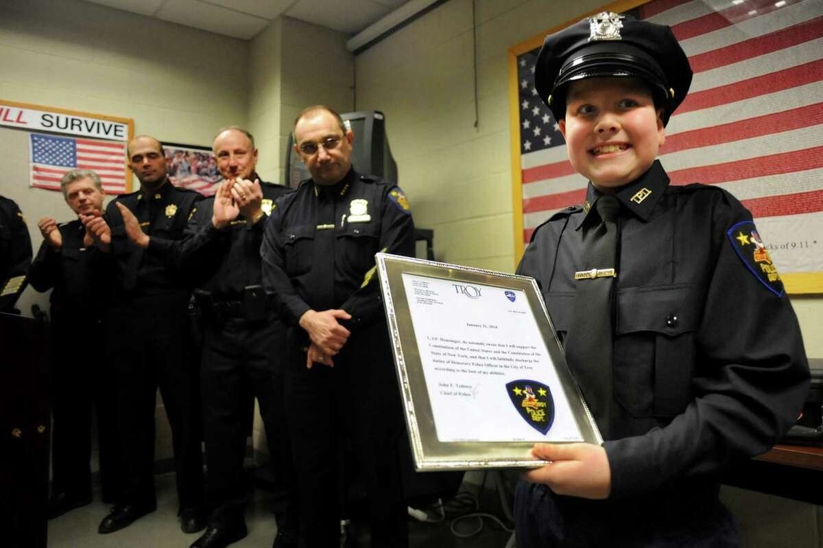 J.P. Honsinger, 10, of Clifton Park, right, stands as a honorary member of the Troy Police force on Friday, Jan. 31, 2014, at Troy Police Headquarters in Troy, N.Y. (Cindy Schultz / Times Union)
