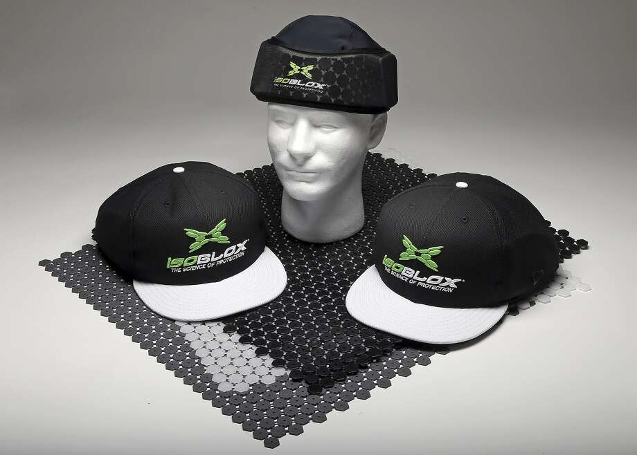 This product image released by Vizion Group on Tuesday, Jan. 28, 20134, shows the isoBLOX protective caps, for professional baseball players, left and right, and a youth level protective skull cap, center, for under a standard fielder's cap, set atop sheets of the actual protective material, uniquely-formulated plates that use a combination of dispersion and absorption techniques to diffuse energy upon impact with a high-velocity object. Major League Baseball has approved the protective cap for pitchers to reduce the effects of being hit in the head by line drives. (AP Photo/Vizion Group) Photo: Associated Press
