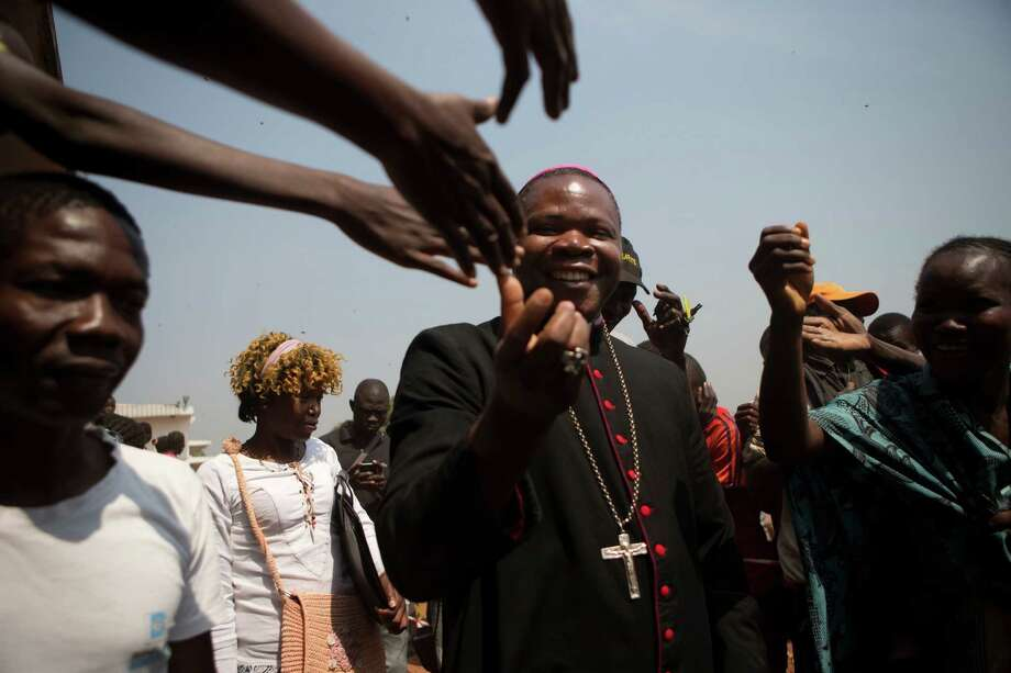 Bangui Archbishop Dieudonne Nzapalainga is greeted by Catholic faithful as he visits an aid distribution point inside a makeshift camp housing an estimated 100,000 displaced people, at Mpoko Airport in Bangui, Central African Republic, Tuesday, Jan. 7, 2014. Tuesday's distribution by the World Food Program and the United Nations Refugee Agency was the first aid delivery to the camp since Dec. 15. Over the last three weeks, the population of the camp has more than doubled, and many families were lacking food or even rudimentary shelter from the harsh daytime sun and chilly nights. (AP Photo/Rebecca Blackwell) ORG XMIT: RLB126 Photo: Rebecca Blackwell / AP