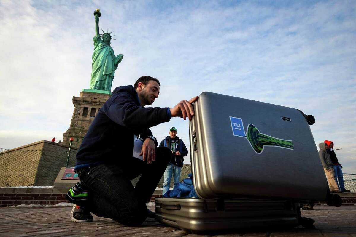 Space Needle employee Sean Marshall, left, opens a case containing a 25-foot by 35-foot 12th Man flag to open under the Statue of Liberty in honor of the Seahawks making it to the Super Bowl Friday, Jan. 31, 2014, on Liberty Island in New York. The flag, just days before flown over the Space Needle, journeyed from Seattle to Manhattan on a cross-country trip. Thousands of Seahawks fans have signed the flag with messages for the team.