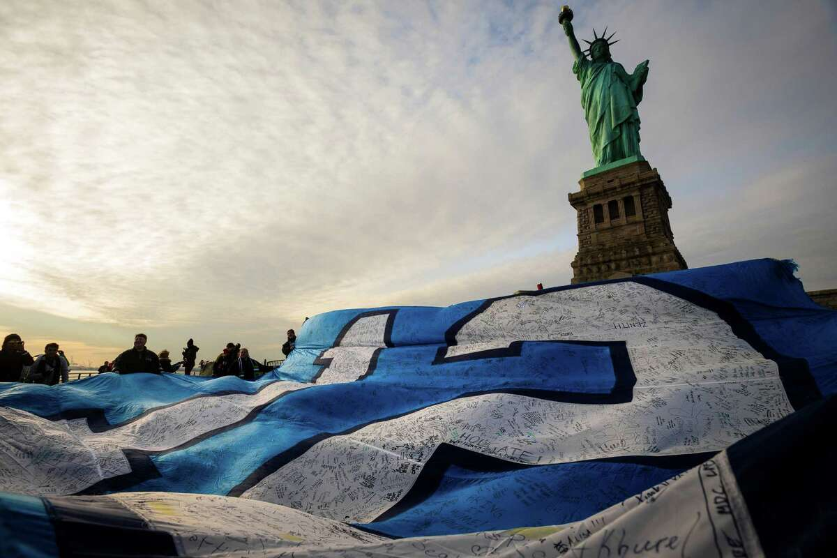 Fans and Space Needle personnel work to unfurl a 25-foot by 35-foot 12th Man flag under the Statue of Liberty in honor of the Seahawks making it to the Super Bowl Friday, Jan. 31, 2014, on Liberty Island in New York. The flag, just days before flown over the Space Needle, journeyed from Seattle to Manhattan on a cross-country trip. Thousands of Seahawks fans have signed the flag with messages for the team.
