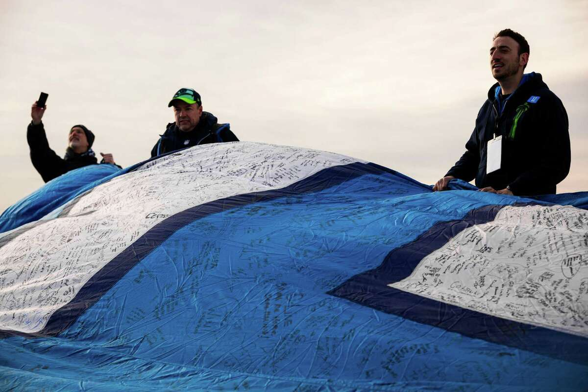 Fans and Space Needle employee Sean Marshall, right, work to unfurl a 25-foot by 35-foot 12th Man flag under the Statue of Liberty in honor of the Seahawks making it to the Super Bowl Friday, Jan. 31, 2014, on Liberty Island in New York. The flag, just days before flown over the Space Needle, journeyed from Seattle to Manhattan on a cross-country trip.