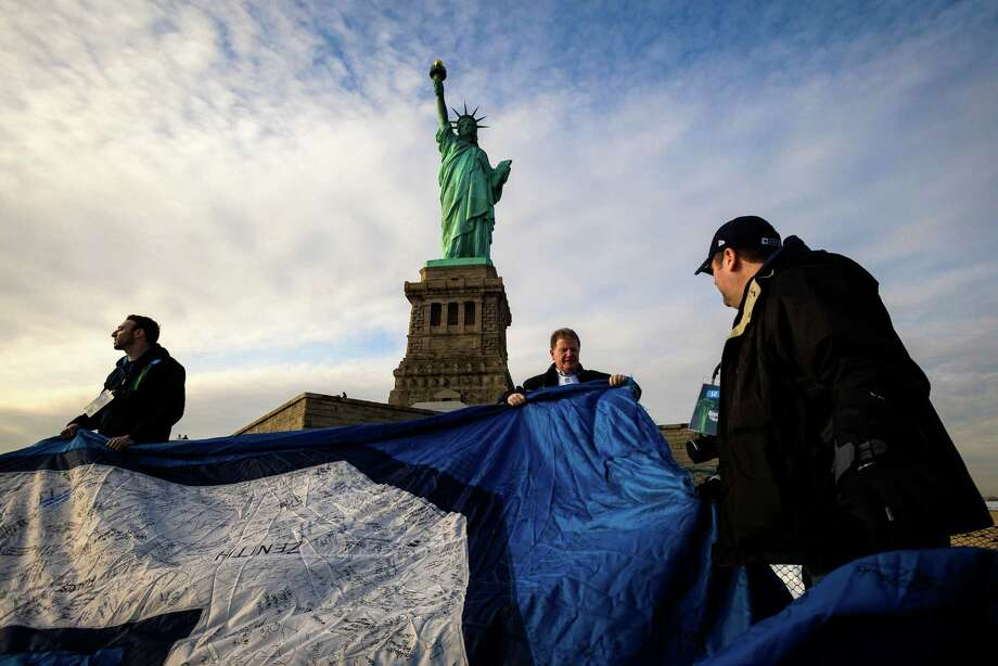 Fans and Space Needle personnel work to unfurl a 25-foot by 35-foot 12th