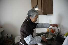 YWCA of San Francisco resident Wai Ying Pang, uses an aerator, installed by the SFPUC, while filling a bowl with water to clean vegetables on Tuesday, January 28, 2014 in San Francisco, Calif.  Pang was demonstrating how she puts water into a bowl, instead of letting the water run,  to clean vegetables which helps save water.
