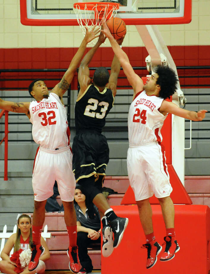 Sacred Heart's #32 De'Aires Tate, left, and teammate #24 Mostafa Abdel Latif, right, try to disrupt a shot by Bryant's #23 Alex Francis, during men's basketball action at Sacred Heart University in Fairfield, Conn. on Thursday January 24, 2013. Photo: Christian Abraham / Connecticut Post