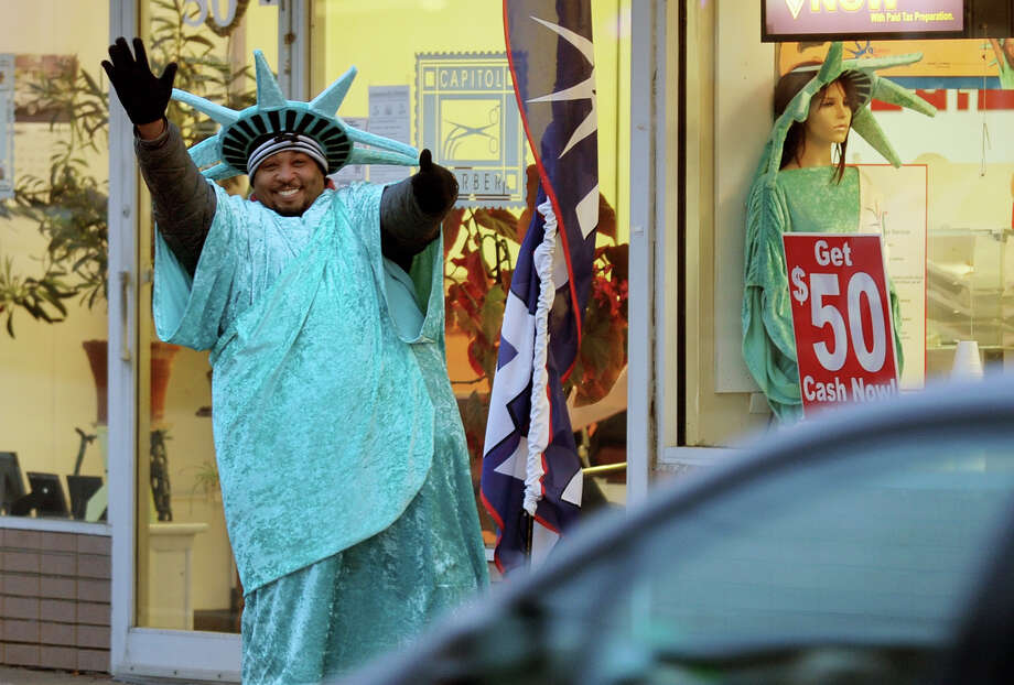 Qushoun Washington, who works for Liberty Tax Services, waves to cars as they pass by on Bridge Street in downtown Ansonia, Conn. on Friday January 31, 2014. Photo: Christian Abraham / Connecticut Post