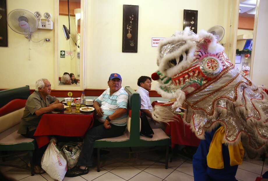 Peru: People dance in a Chinese lion costume inside a restaurant celebrating the Chinese Lunar New Year in the Chinatown area of Lima, Peru, Friday, Jan. 31, 2014. Friday marks the beginning of Chinese Lunar New Year, the year of the horse, according to Chinese astrology. Photo: Martin Mejia, Associated Press