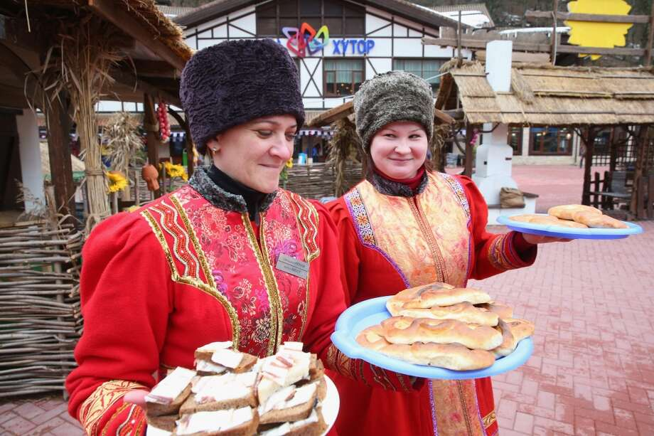 Russia: Woman dressed in their traditional Russian outfit serve local food at the center of the Rosa Khutor Mountain Cluster village ahead of the Sochi 2014 Winter Olympics on January 31, 2014 in Rosa Khutor, Sochi. Photo: Alexander Hassenstein, Getty Images