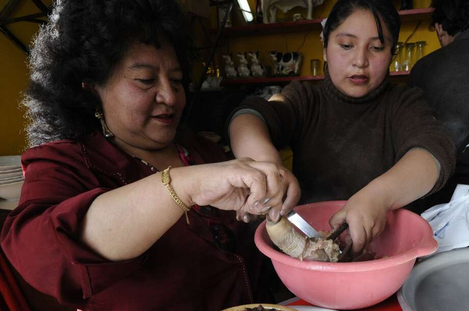 "Bolivia:  The owner of the Casa de Oro restaurant Aydé Urquizo Jauregui (L) serves ""Cardan"" --a soup made with phallus and testicles of bulls-- in La Paz. For Bolivian people, this soup has aphrodisiac qualities among other powers. Photo: Jorge Bernal, AFP/Getty Images"