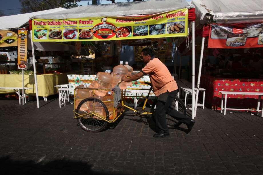 Mexico: A vendor pushes his bicycle cart filled with 18-liter jugs of bottled water to sell to owners of street food stalls in Mexico City. Photo: Marco Ugarte, Associated Press
