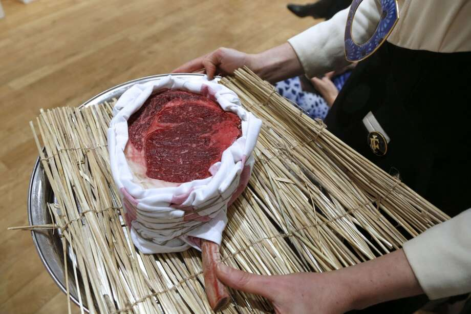 "France: A woman presents a rib Wagyu ""100 days of maturation"" from the house Yves-Marie Le Bourdonnec during a sale of fine food to raise funds for the French Red Cross. Photo: Francois Guillot , AFP/Getty Images"