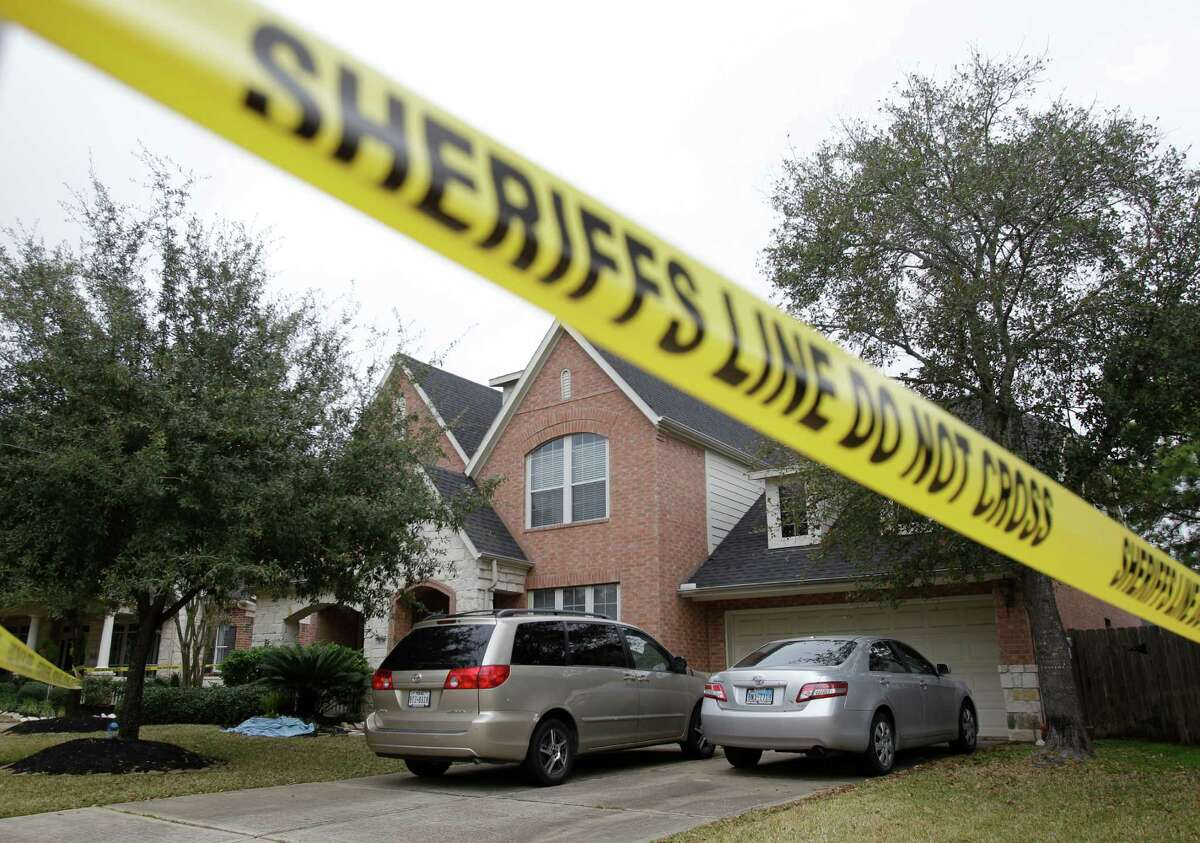 Crime scene tape surrounds a home in the 14000 block of Fosters Creek Dr. Friday, Jan. 31, 2014 in Cypress where four people where found dead inside on Thursday.