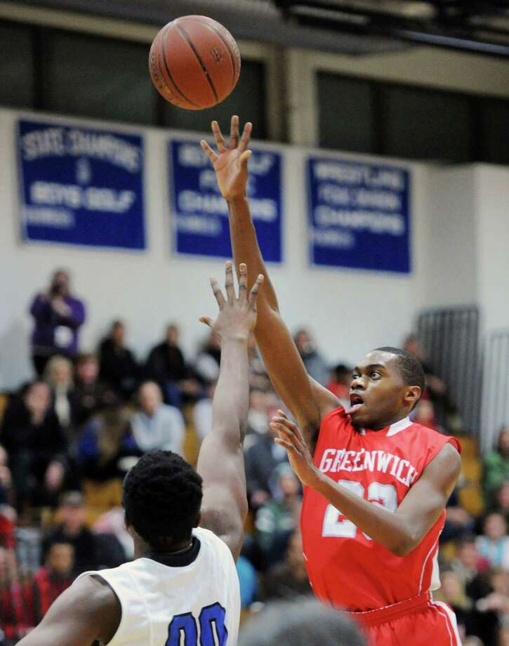 At right, Leonel Hyatt (#23) of Greenwich scores on Darien's Chima Azuonwu (#00) during the boys high school basketball game between Darien High School and Greenwich High School at Darien, Friday night, Jan. 31, 2014. Photo: Bob Luckey / Greenwich Time