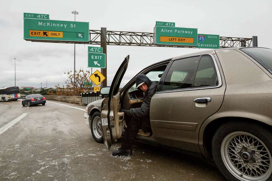 Riogo Rodriguez tries to back his car out after becoming stranded for over two hours on the McKinney St. exit ramp off of I-45 due to icy road conditions that snarled the morning commute, Friday, Jan. 24, 2014, in Houston. (AP Photo/Houston Chronicle, Michael Paulsen) Photo: Michael Paulsen, MBI / Houston Chronicle
