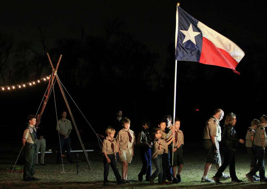 Boy Scouts Pack 1179 retire the flags after a candlelight vigil on Friday honoring the Cypress family found dead in their home the night before.  The vigil was held near a community center soccer field along Barker Cypress. One of the victims was a Scout member. Photo: Mayra Beltran, Houston Chronicle / © 2013 Houston Chronicle