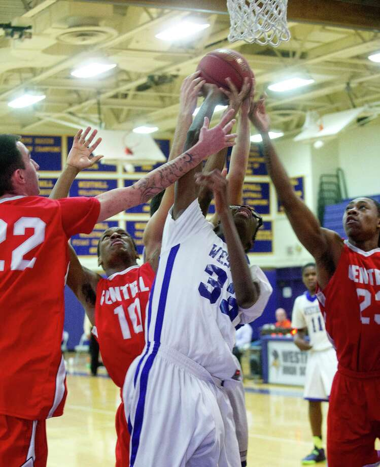 Westhill's Brendon Thomas is surrounded by Bridgeport Central players as they all reach for the rebound during Friday's basketball game at Westhill High School on January 31, 2014. Photo: Lindsay Perry / Stamford Advocate