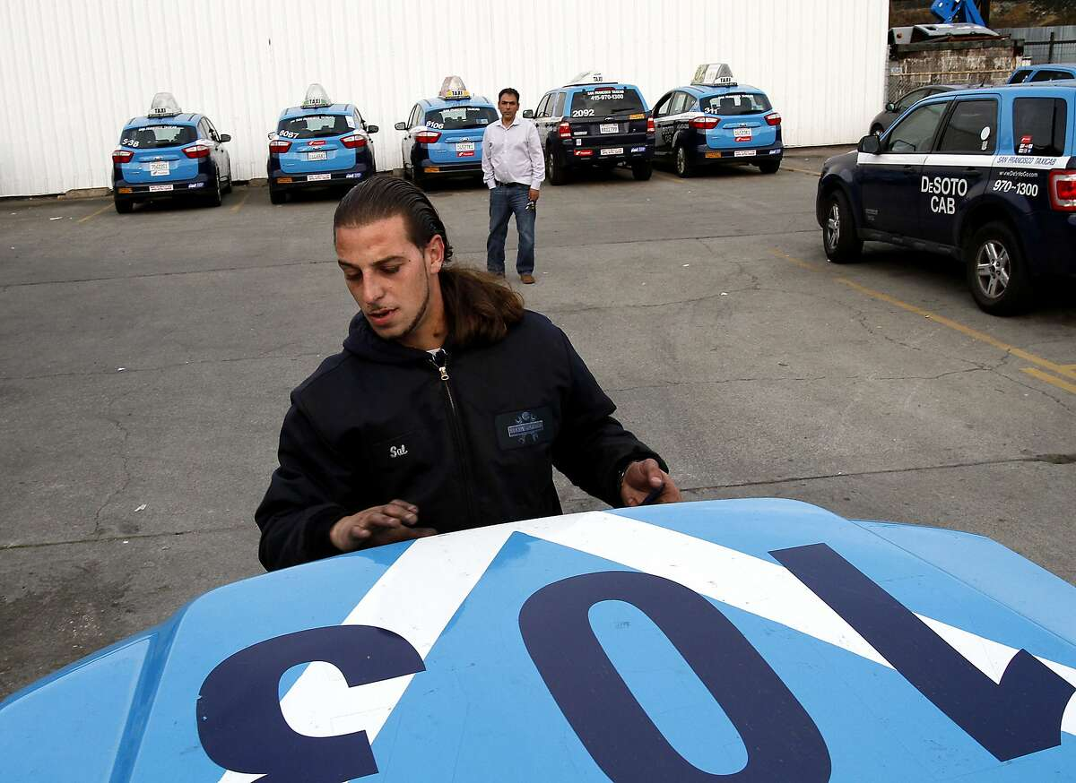 Sal Albowyha checks under the hood of one of the DeSoto cabs at the end of its shift at their garage in San Francisco, Calif., on Monday, January 27, 2014.