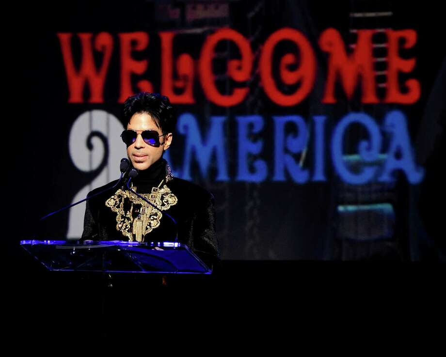 """FILE - In this Oct. 14, 2010 file photo, musician Prince holds a news conference at The Apollo Theater announcing his """"Welcome 2 America"""" tour in New York. Prince turns off the lights at South by Southwest on Saturday night, Match 16, 2013, with an unexpected and intimate showcase that ranks among the biggest surprises in years at the star-studded music festival and conference.  (AP Photo/Peter Kramer, File) Photo: Peter Kramer, FRE / AP"""