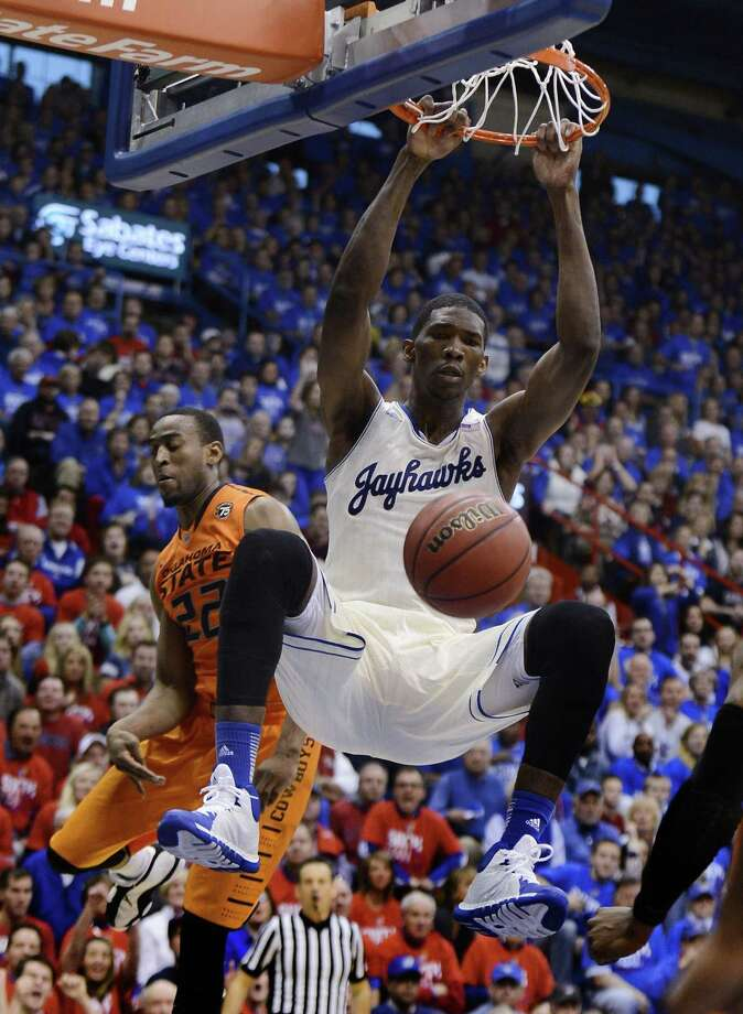 Kansas' Joel Embiid dunks against Oklahoma State's Markel Brown, left, during the second half at Allen Fieldhouse in Lawrence, Kan., on Saturday, Jan. 18, 2014. Kansas won, 80-78. (Rich Sugg/Kansas City Star/MCT) Photo: RICH SUGG, MBR / Kansas City Star
