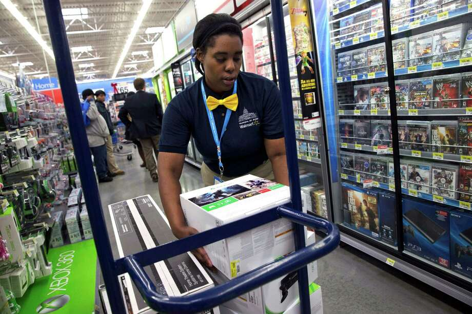 Tracey Anderson restocks Xbox sets at a Walmart in Washington. Wal-Mart Stores said Friday its fourth-quarter earnings may be below prior forecasts. Photo: Jacquelyn Martin, STF / AP