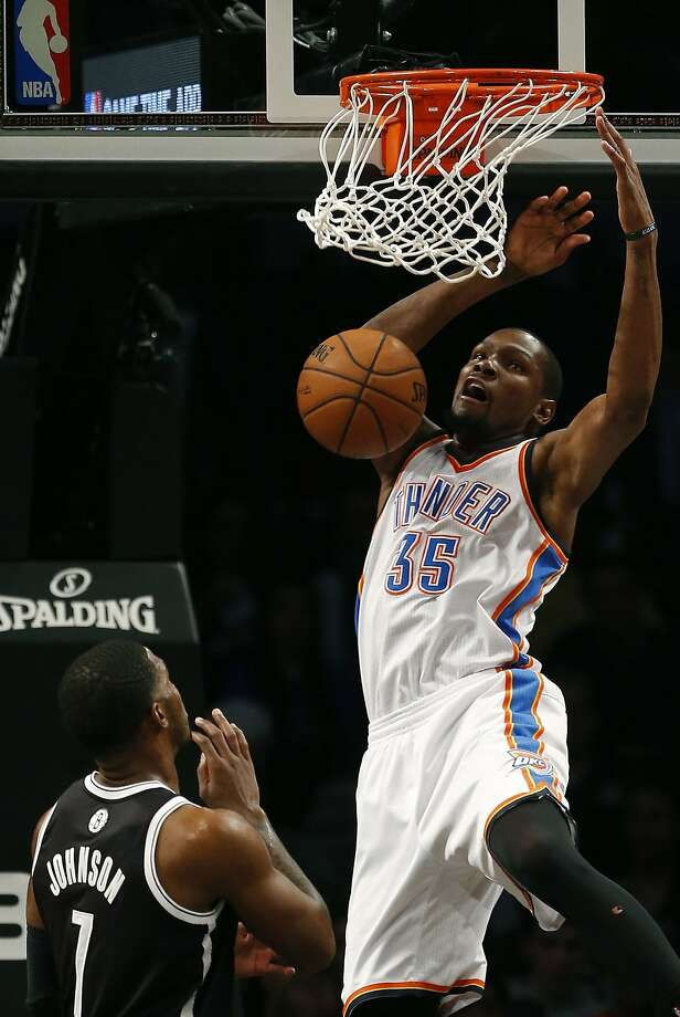 Kevin Durant dunks in front of Brooklyn's Joe Johnson, but came up four points short of his 13th straight 30-point game. Photo: Noah K. Murray, Reuters
