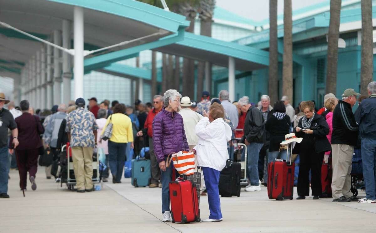 Passengers wait for their rides Friday after getting off the Caribbean Princess, which returned early with norovirus reported on board.