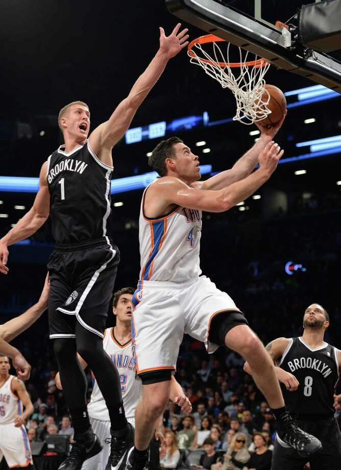 Nick Collison of the Oklahoma City Thunder (R) drives against Mason Plumlee of the Brooklyn Nets (L) during their NBA game January 31, 2014 at the Barclays Center in the Brooklyn borough of New York. Oklahoma City won, 120-95. AFP PHOTO/Stan HONDASTAN HONDA/AFP/Getty Images ORG XMIT: 182415857 Photo: STAN HONDA / AFP