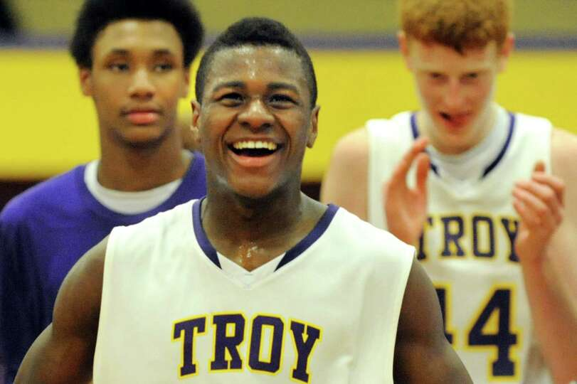 Troy's Dyaire Holt, center, celebrates their 81-73 overtime win over Catholic Central on Friday, Jan