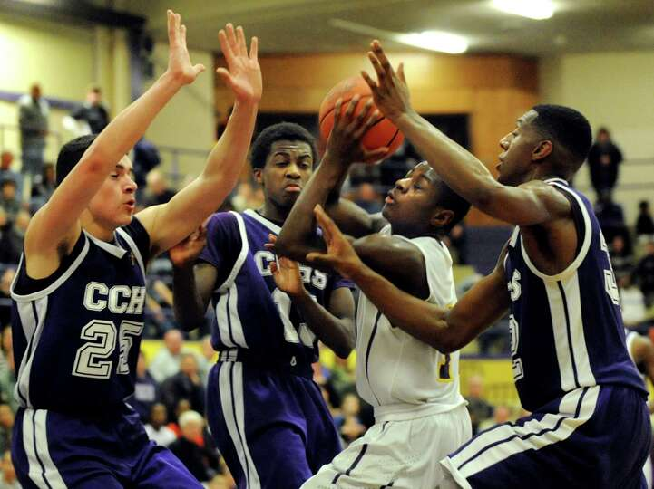 Troy's Dyaire Holt, center, fights off Catholic Central's defense during their basketball game on Fr