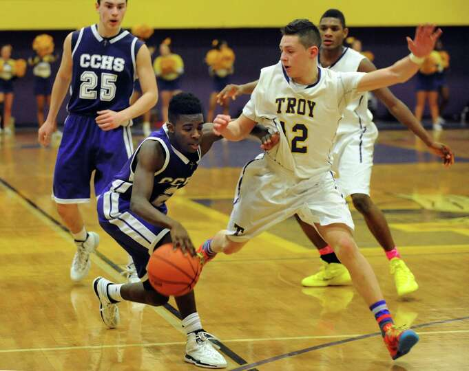 Catholic Central's Raiquis Harrs, center, controls the ball as Troy's Zach Radz defends during their